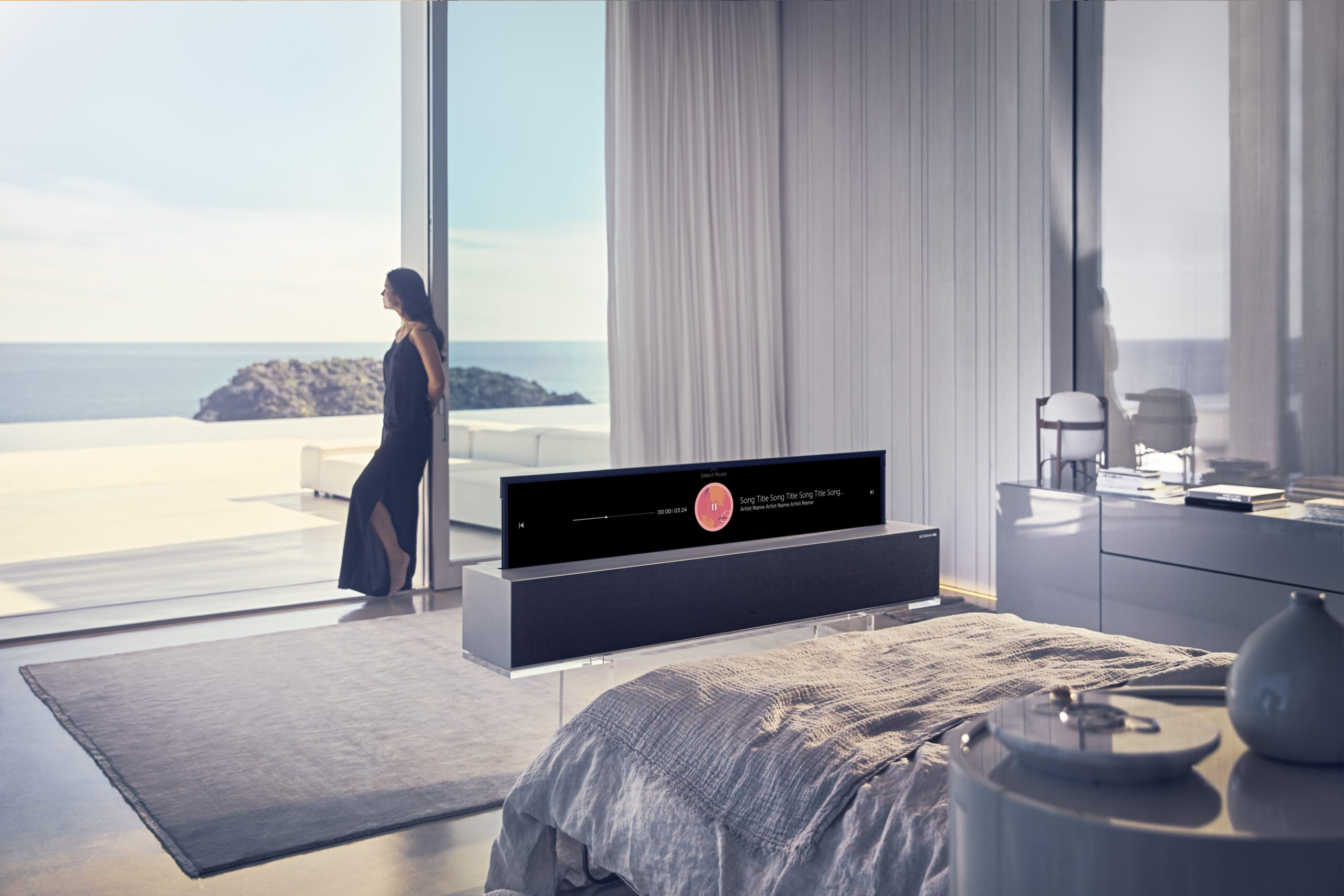 A woman looking out of the window while an LG SIGNATURE OLED TV R is at the foot of the bed displaying the music playlist.