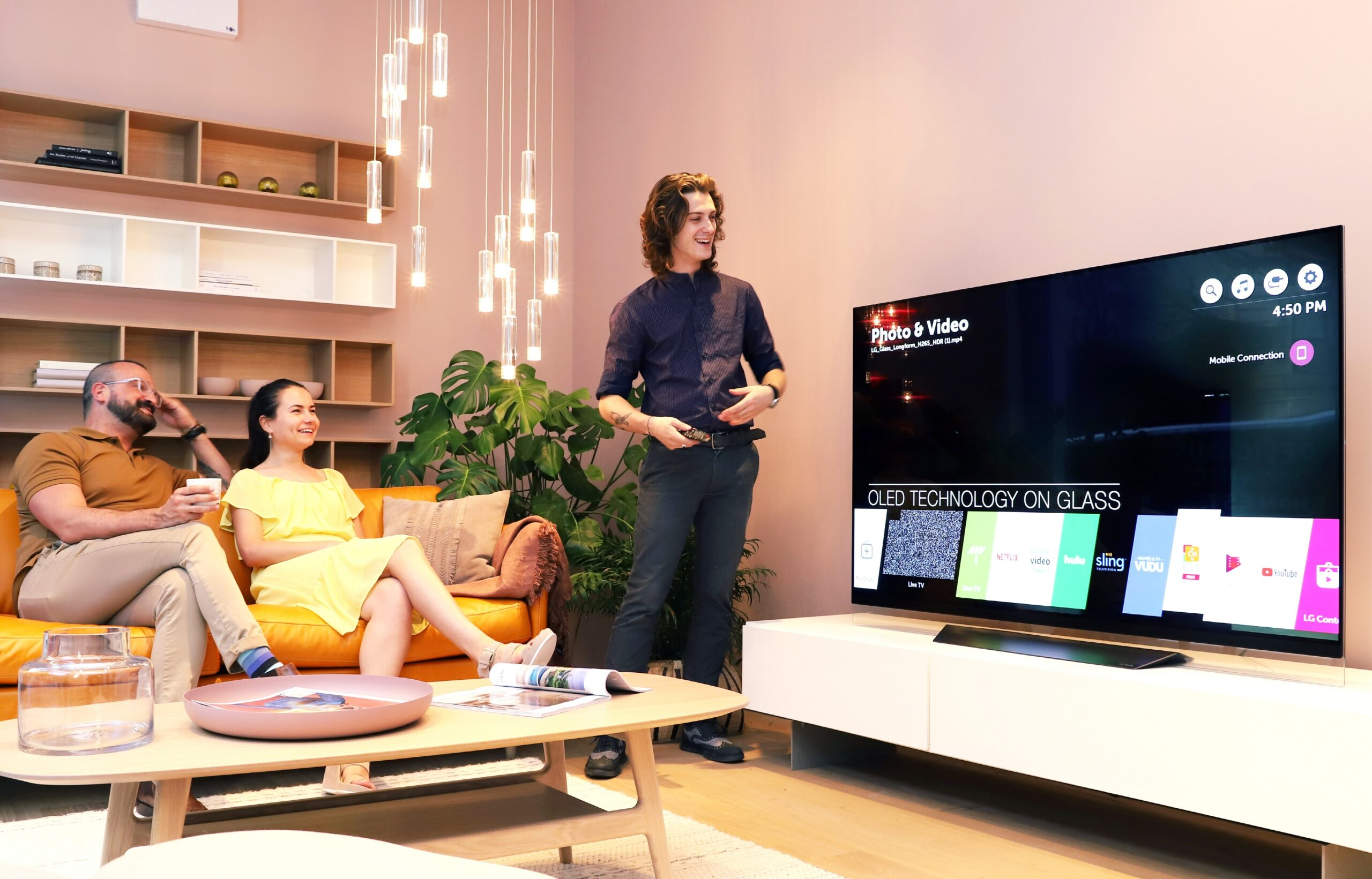 A male attendant tries out the AI assistant features of LG's ThinQ-eabled OLED TV which displays the application bar of webOS platform on the screen