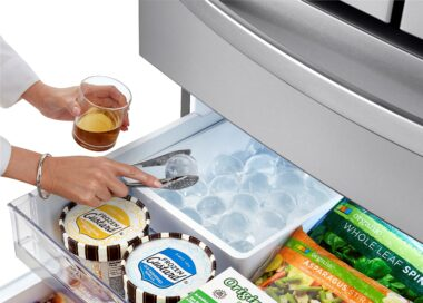 A woman takes an ice ball from the LG refrigerator's Craft Ice Maker to chill her drink