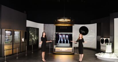 Two female models point at the prototypes of the LG SIGNATURE lineup at the display zone of CES 2019.
