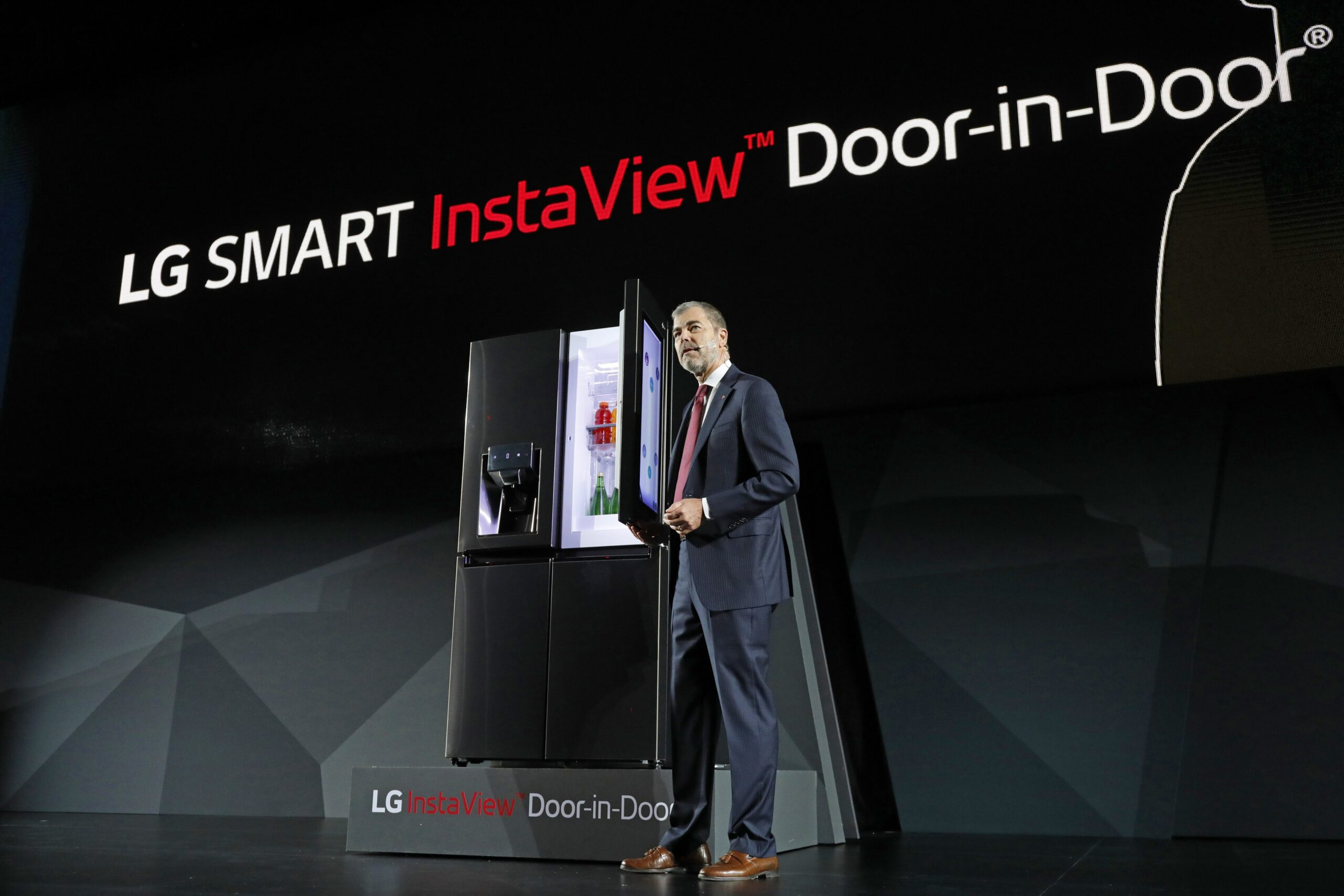 David VanderWaal, Senior Vice President, Marketing, LG Electronics opens the door of LG's InstaView Door-in-Door refrigerator at its CES 2017 Press Conference.