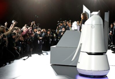 Side view of a female model posing with LG CLOi Robots on stage while reporters take pictures at LG's CES 2017 Press Conference.
