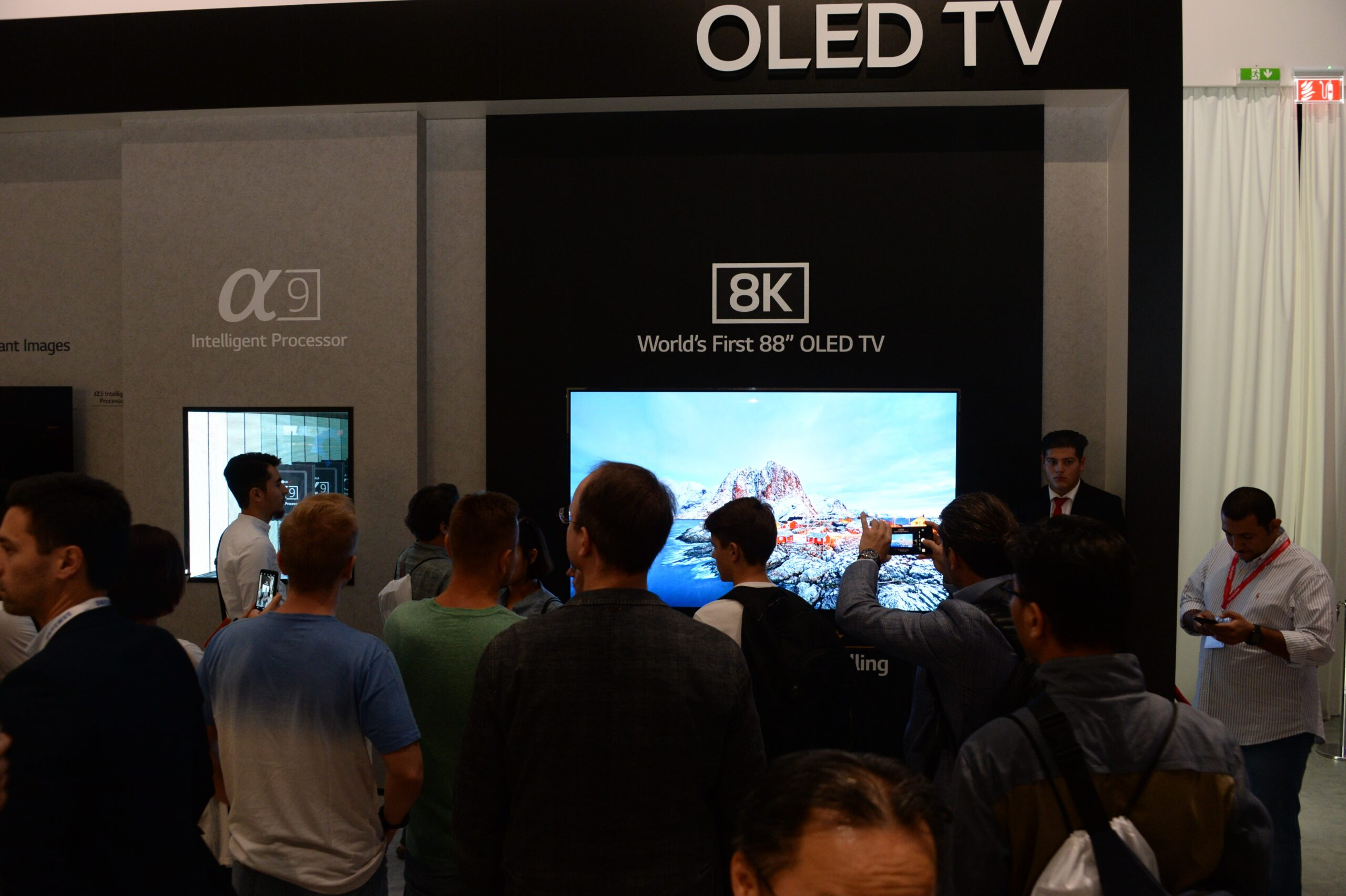 World's First 8K OLED TV with A9 Intelligent Processor display zone at IFA 2018 with conference attendees walking around and looking at the display