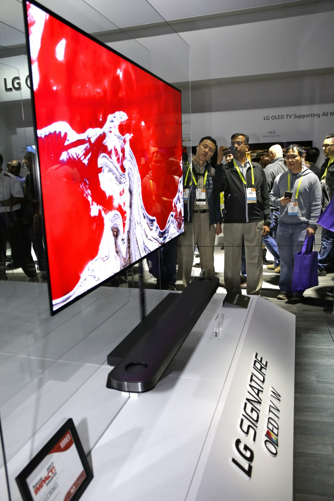 Side view of LG SIGNATURE OLED TV W display with conference attendees examining its incredibly thin display at the model at CES 2017