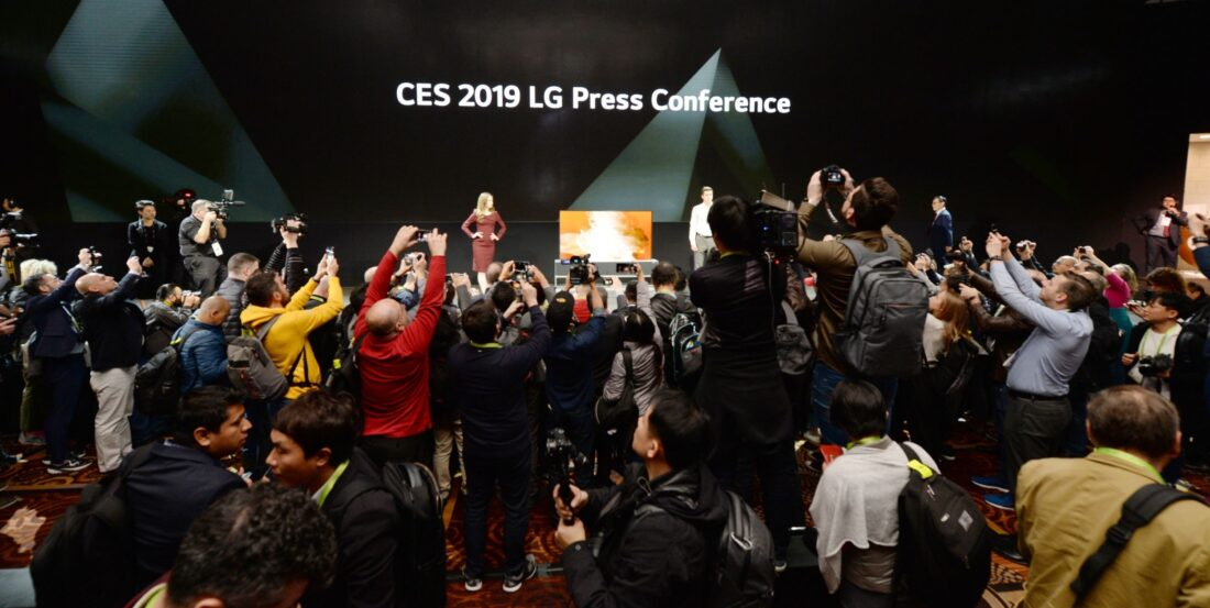 Far shot of the CES 2019 LG Press Conference with a pair of male and female models onstage posing while reporters are recording and taking pictures