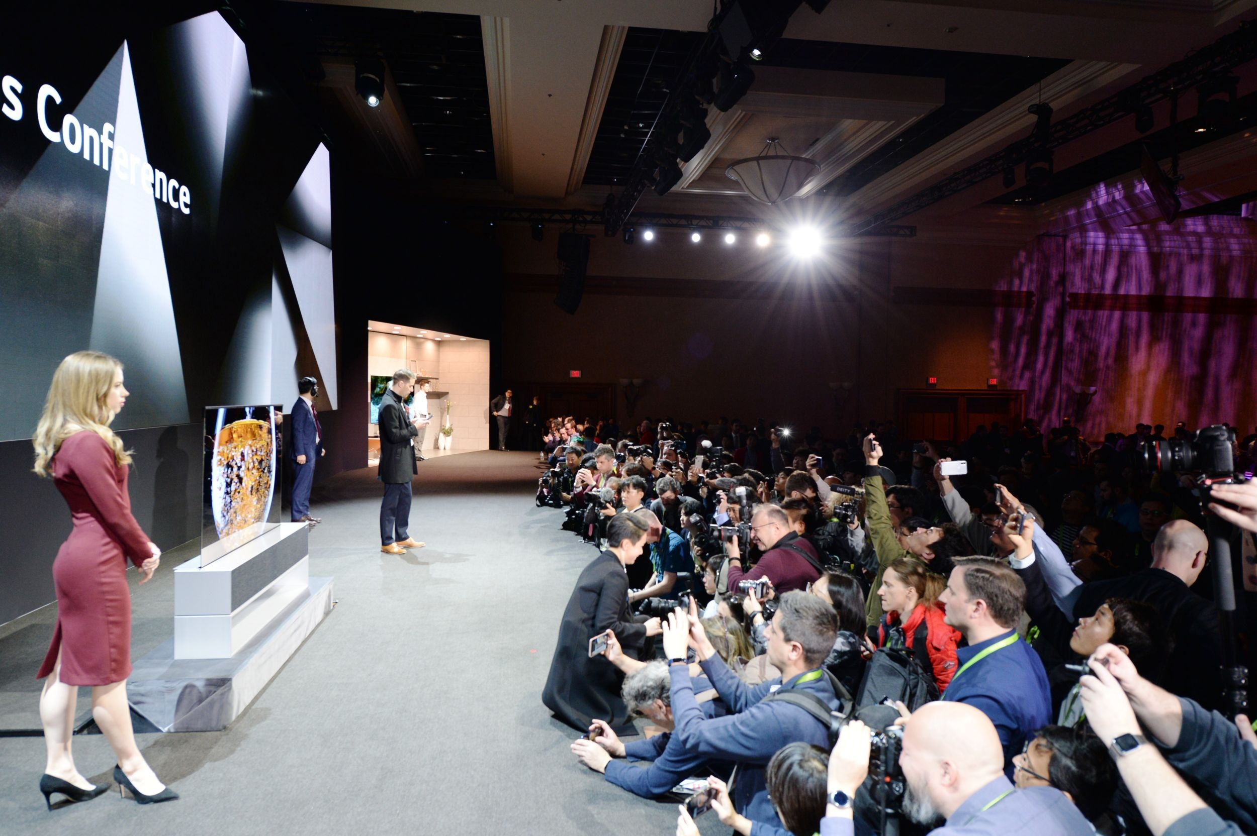 Side view of the CES 2019 LG Press Conference with a pair of male and female models onstage posing while reporters are recording and taking pictures