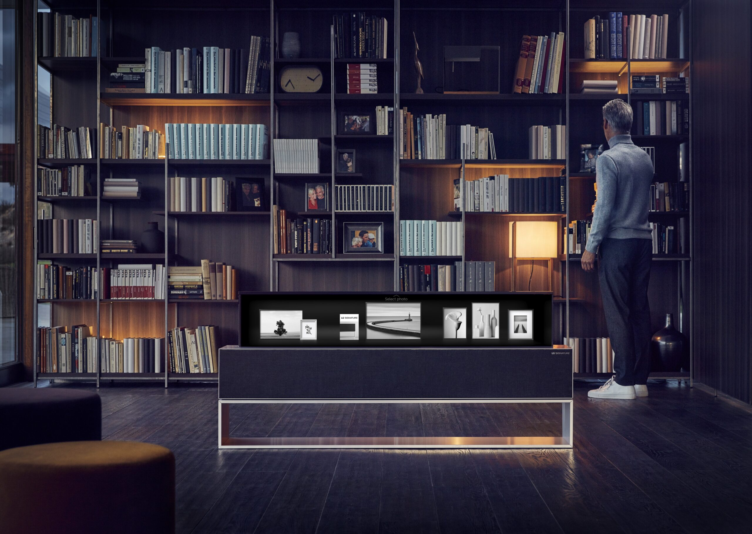 A man is browsing his bookshelf, an LG SIGNATURE OLED TV R enhances the environment by displaying photos on its screen