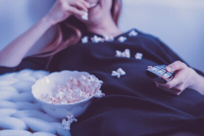 A woman holding the TV remote while eating popcorn