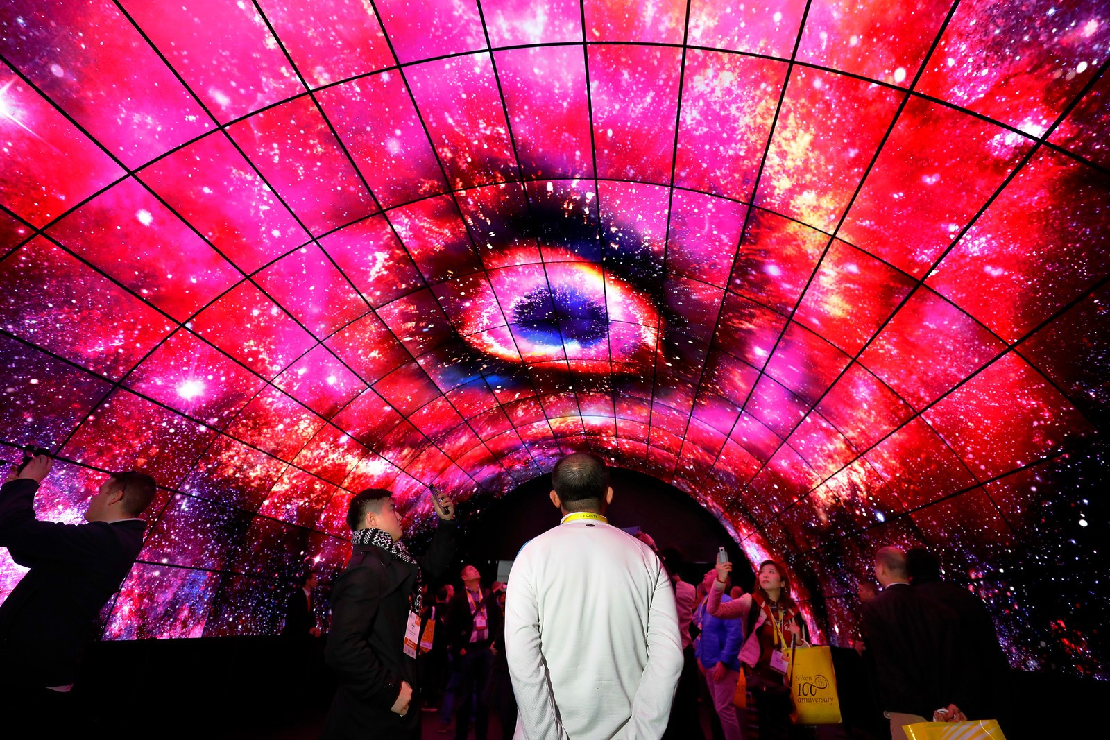 Visitors look up at the OLED screens of the LG OLED Tunnel at LG's CES 2017 booth
