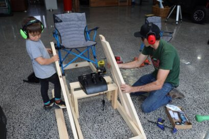 Rick Kelly and his son in the act of building their at-home racing simulator