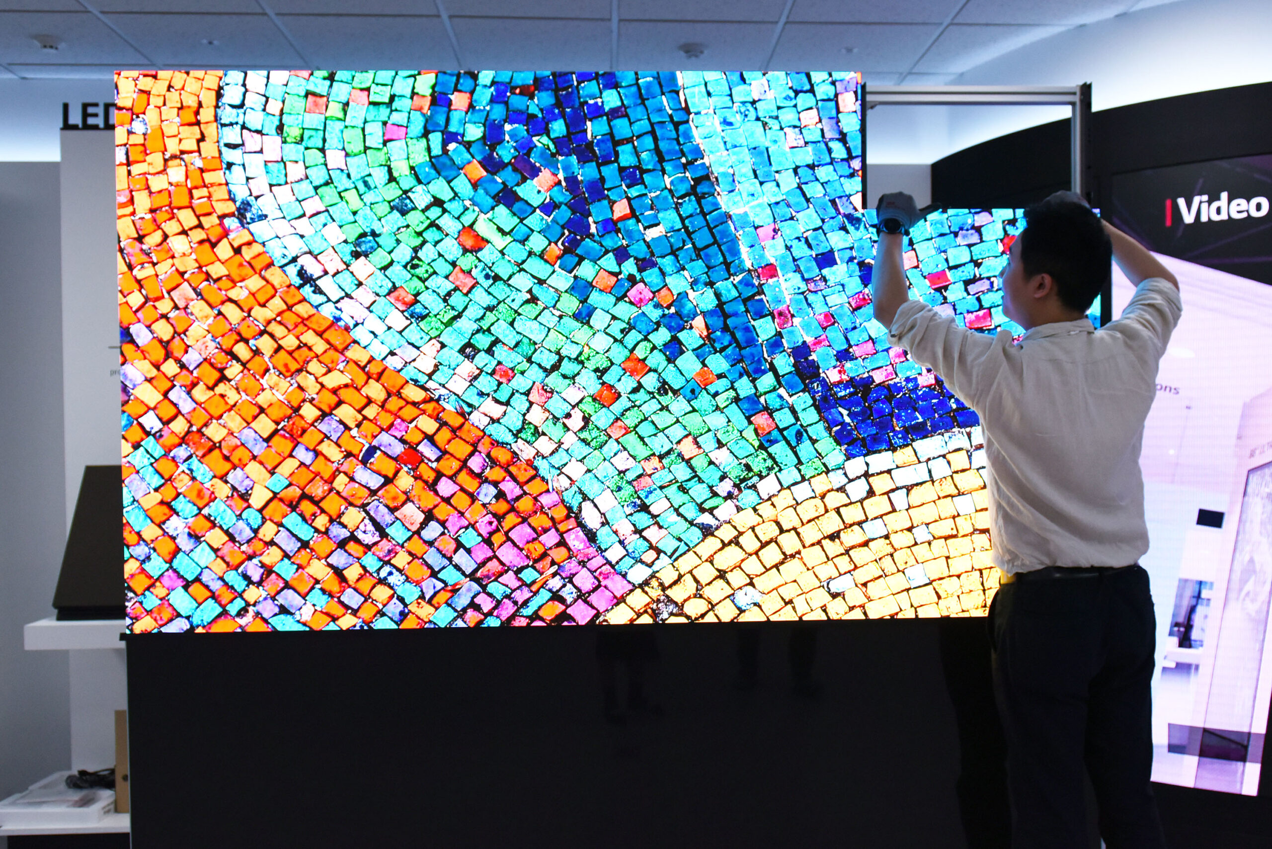A man installing the LG LED Signage (LSAA) demonstrates how perfectly and easily each panel fits together to make a vibrant, high-quality large display