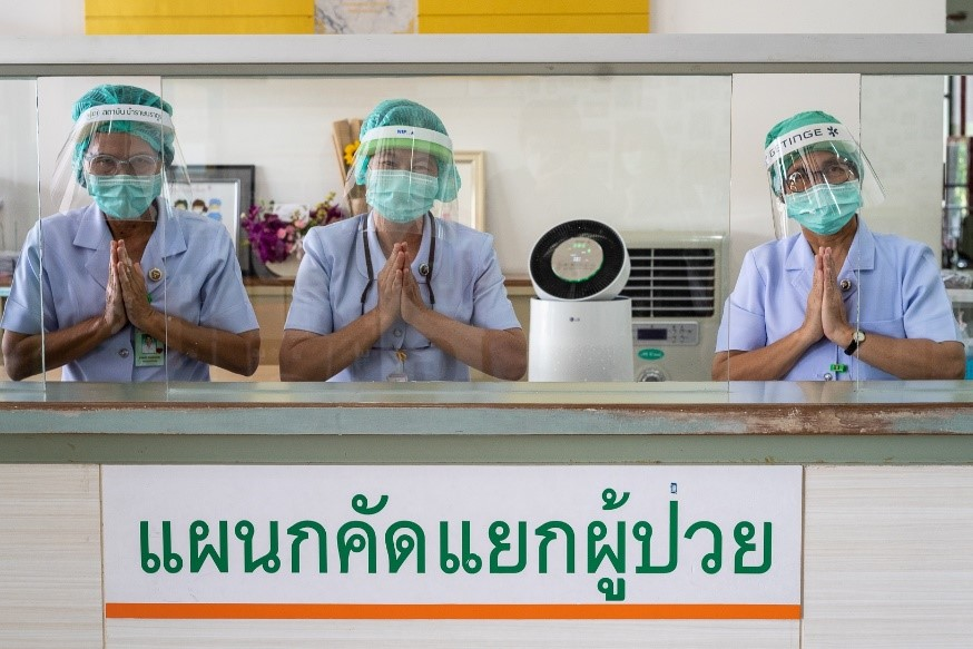 Three medical workers showing their gratitude in front of an LG PuriCare air purifier