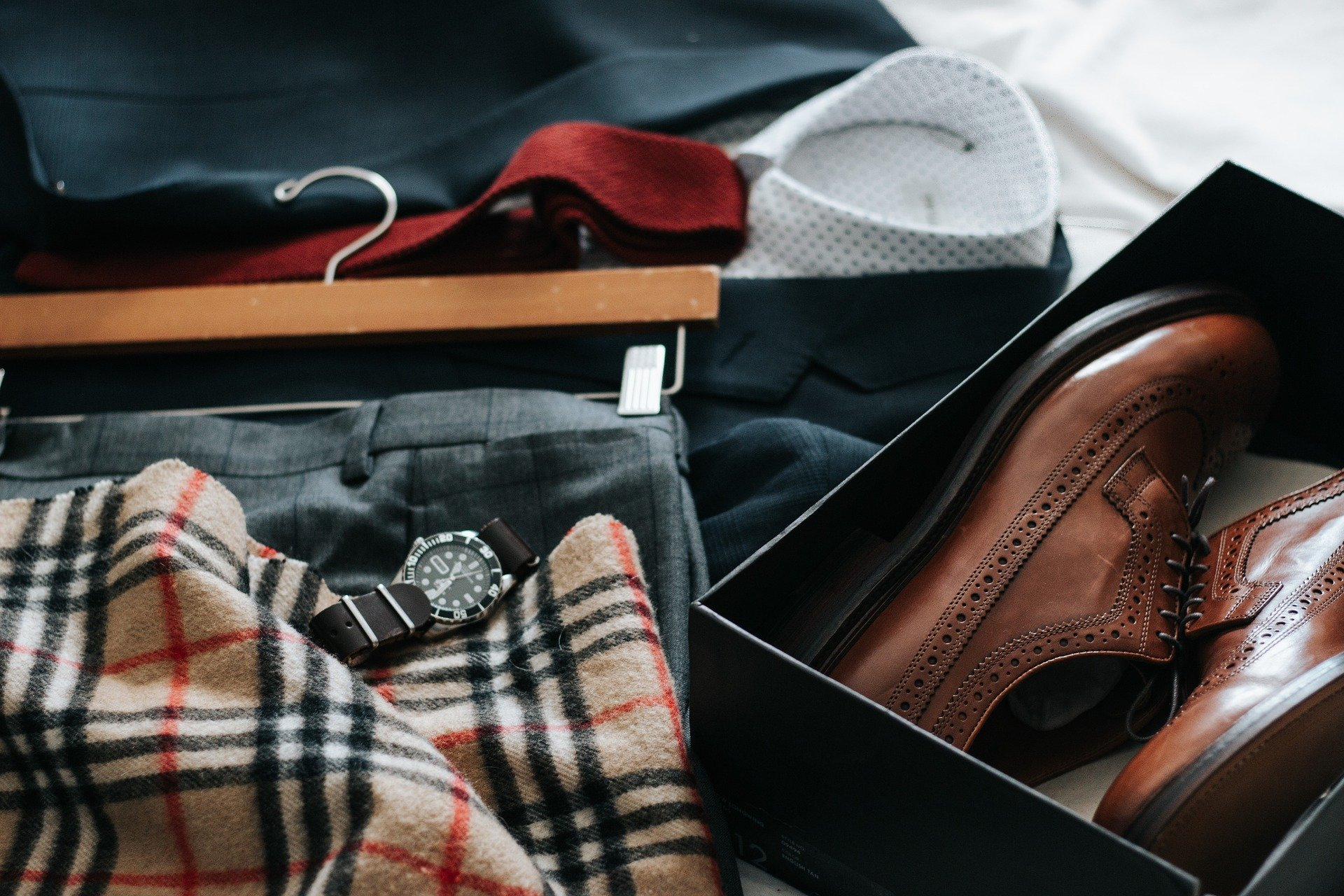 An array of smart clothes and shoes laid on a bed