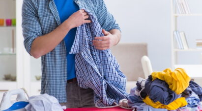 A man prepares to iron out the wrinkles in his clothes