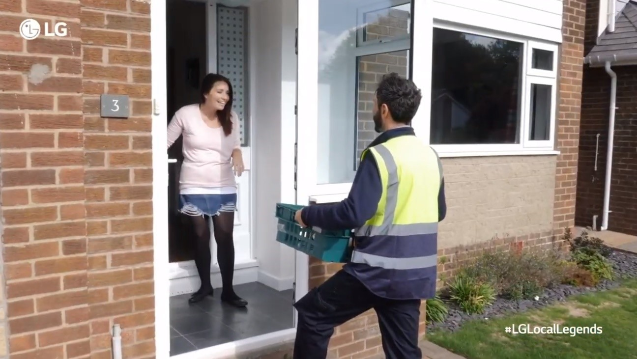 A woman looks overjoyed as a man pays a visit to her front door to gift a large box of groceries