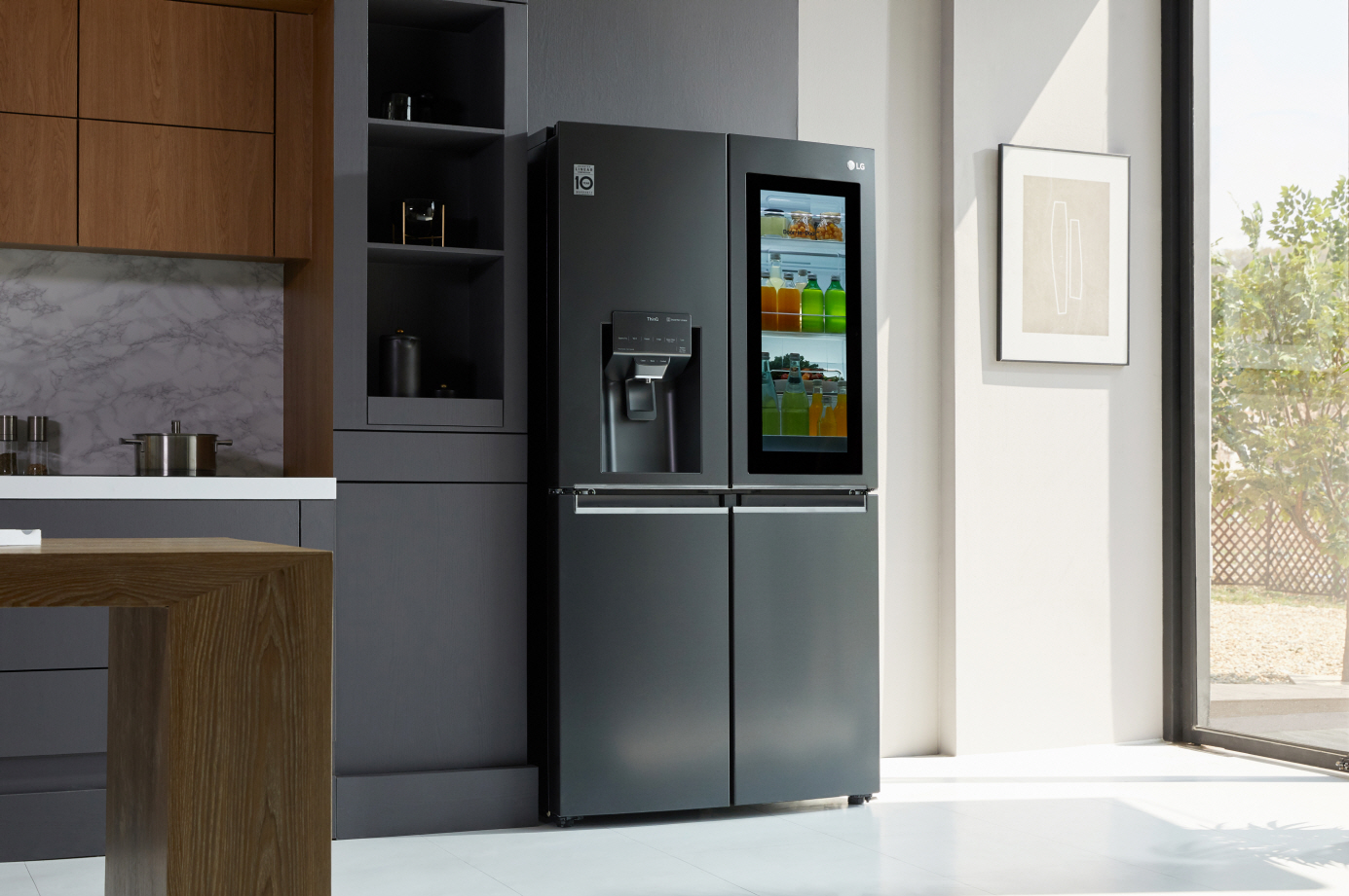 A kitchen with LG InstaView Door-in-Door refrigerator with UVnano showing its inside with InstaView becoming transparent