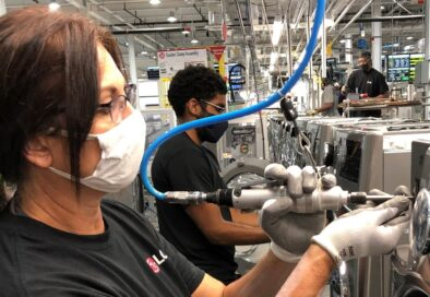 One LG factory worker using special equipment to assemble the washing machine's front panel while others work in the background