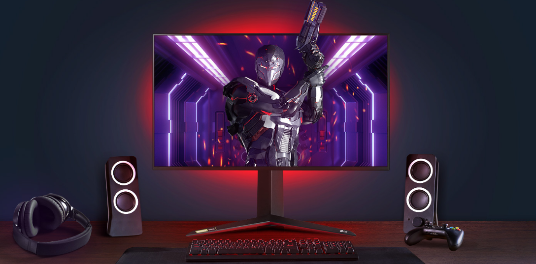 A complete gaming setup with LG UltraGear as the centerpiece, the monitor's back lights shining bright red and the game character bursting out of the display