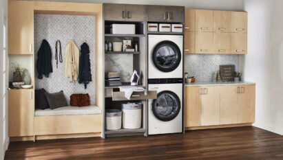The white LG WashTower fitted inside a modern room with wooden furnishings and next to a space designed for ironing and storing dirty laundry