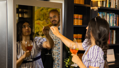 Two attendees to the LG SIGNATURE Goodwood races event check out the LG SIGNATURE Wine Cellar while testing its InstaView feature by knocking on its glass panel