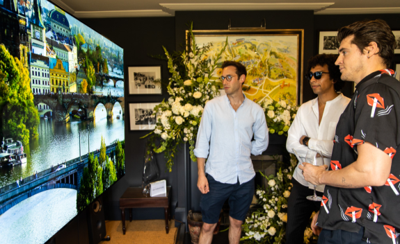 Three male attendees of SIGNATURE's Goodwood event take a closer look at the clear, vivid imagery provided by the LG SIGNATURE 77-inch OLED TV