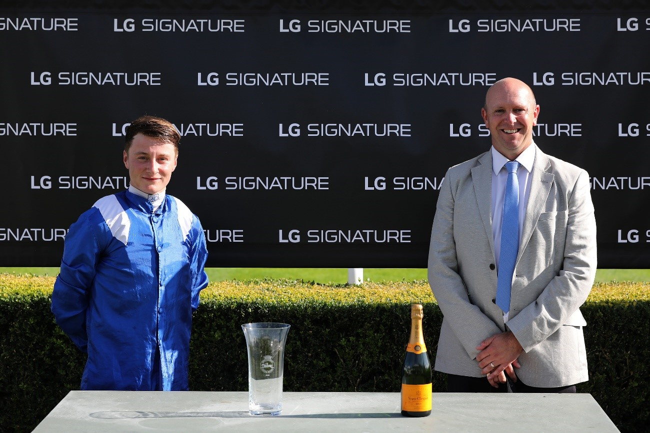 A winning jockey from the Qatar Goodwood Festival is presented with a glass trophy and a bottle of champagne in front of an LG SIGNATURE-branded sign