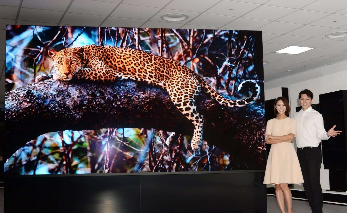 A front view of the LG MAGNIT's screen displaying a majestic leopard with a man and woman posing beside it