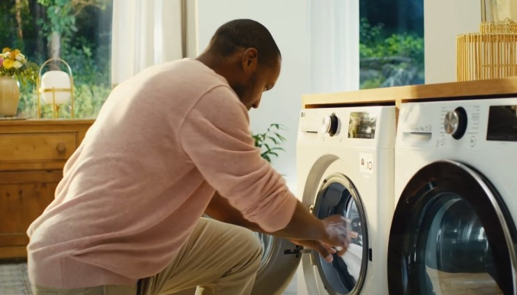 A man taking clothing out of his LG washing machine
