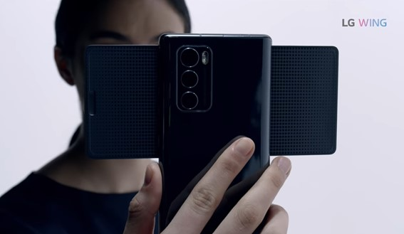 A person holds LG WING in Swivel Mode with the three rear camera lenses clearly seen