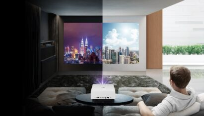 A man uses LG CineBeam in his living room to view a vivid day & night Kuala Lumpur skyline in both light and dark room conditions
