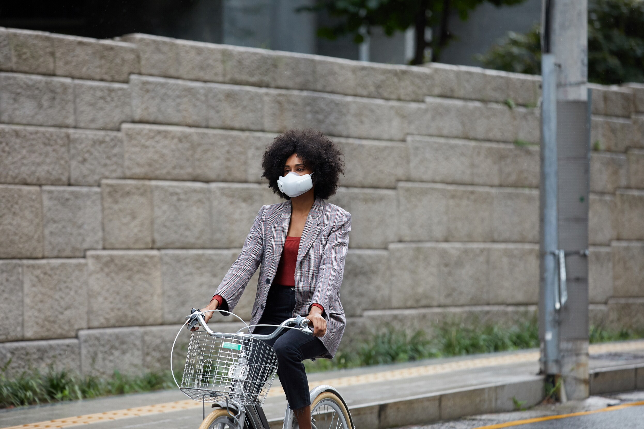 A woman on a bicycle wearing LG PuriCare™ wearable Air Purifier