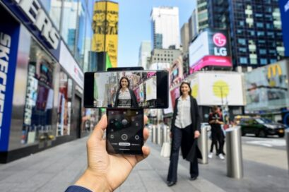 A person taking a picture of a woman walking toward the camera in Times Square with the help of LG WING's Swivel Mode capabilities