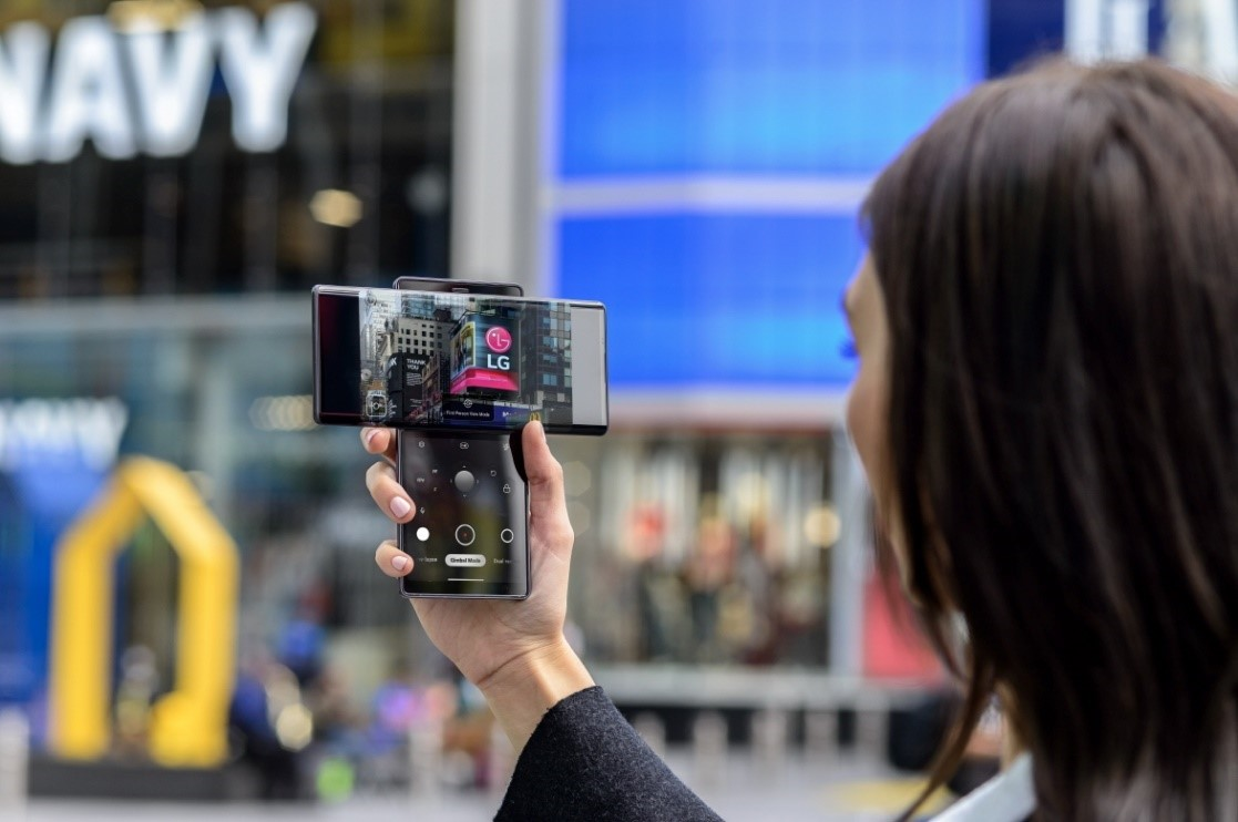 A woman taking a picture of the LG advertisement screen displayed in Times Square with LG WING in Swivel Mode