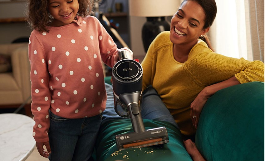 A mother watches on as her daughter uses LG CordZero A9 to vacuum the living room sofa
