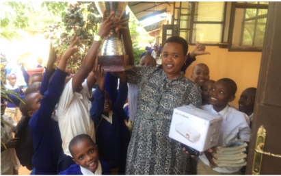 A teacher and students of a Tanzanian elementary school holding up FC Cambounet's trophy and the LG CineBeam projector donated to them to provide a better educational environment.