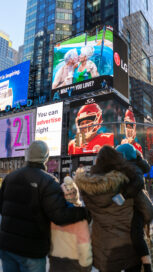 A family pause while walking through Times Square to watch the documentary on LG's giant commercial display.