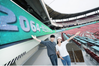 A man and a woman pose in front of LG's LED Signage at KT Wiz Baseball Park in Suwon, Korea.