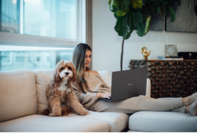A woman working comfortably with the slim and light LG gram on her living room sofa with her dog by her side.