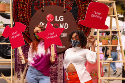 Two people holding up signs to help promote The Second Life Campaign and encourage more people to donate and upcycle their clothing